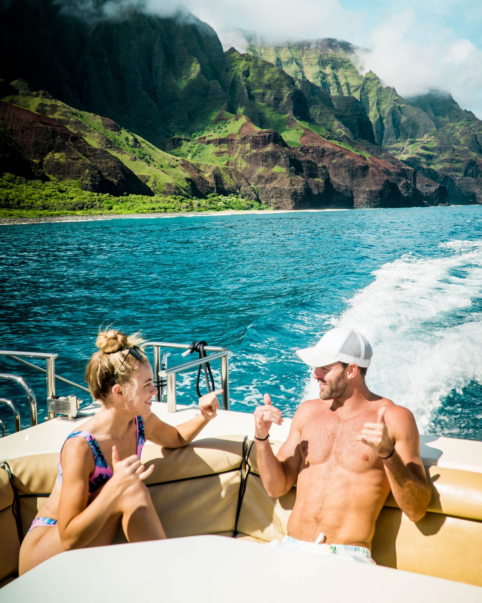 Girl and Guy on a Boat in Tropical Waters with Mountains
