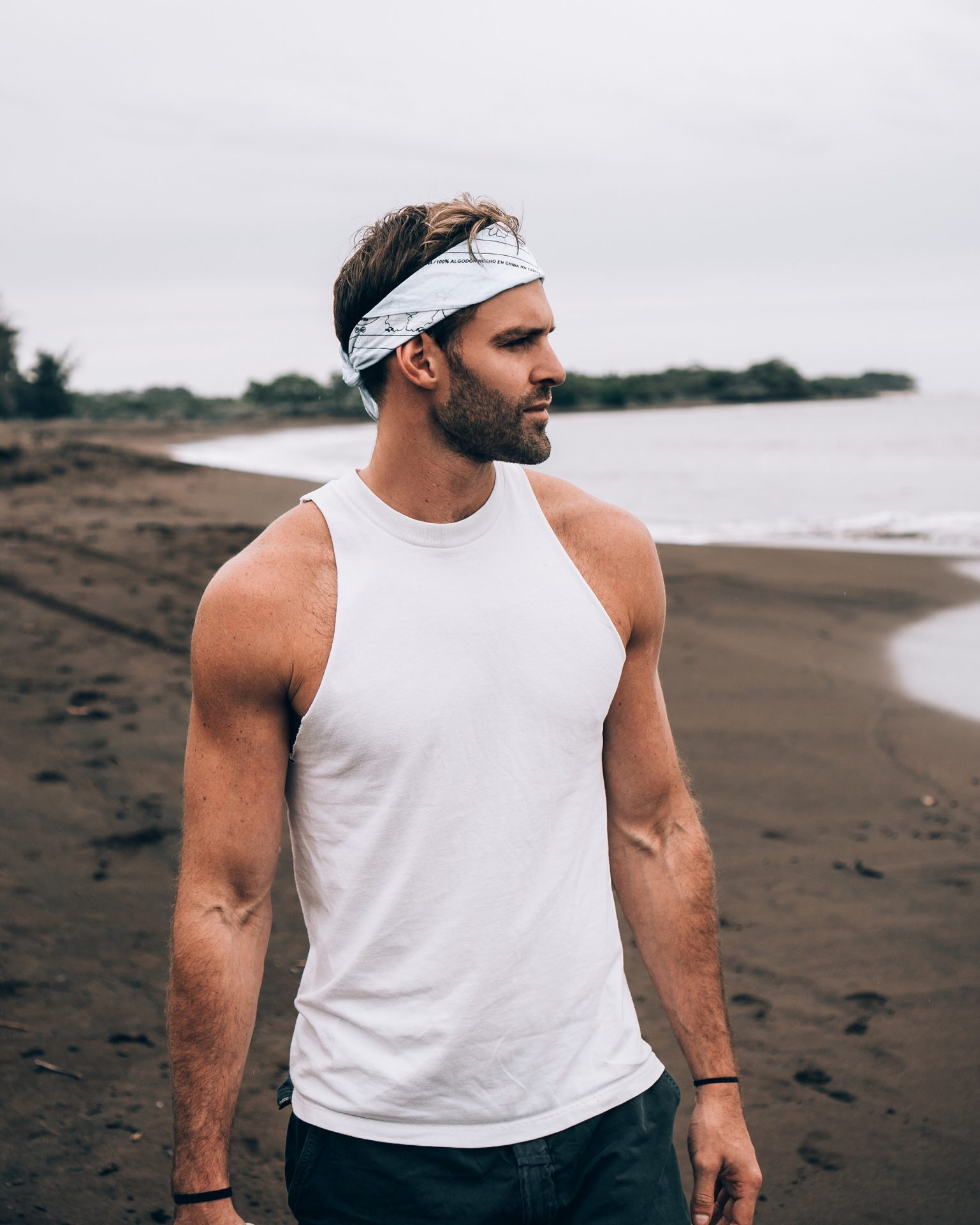 Guy on Beach Wearing White Bandanna, White Tank Top, and Jeans
