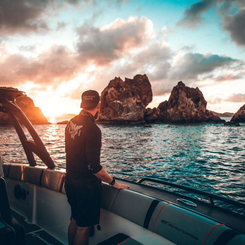 Guy on Midnight Charters Boat Looking at Sunset